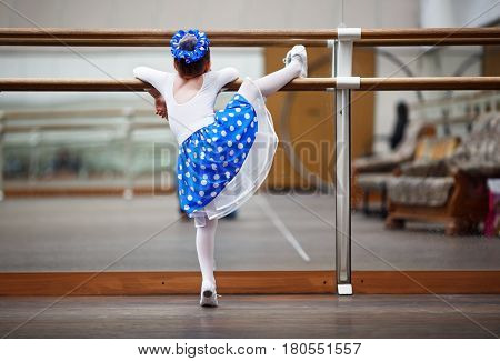 Child girl preparing for a dance performance in the ballet class. Little girl ballerina practicing in a dance class. Preschool child taking dance lessons. Shallow depth of field. Selective focus.