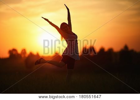 Woman with arms raised dancing against the sunset background. Shallow depth of field. Selective focus on model.