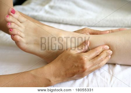 A woman receiving foot reflexology as part of a holistic massage treatment