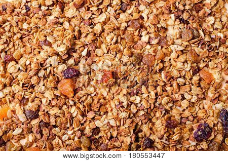 Homemade granola with honey, oatmeal, nuts, raisin, cranberry and dried apricots for background, top view