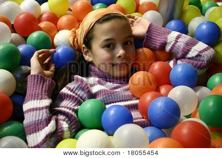 A young girl submerged in the ball pen, surrounded by colorful plastic balls
