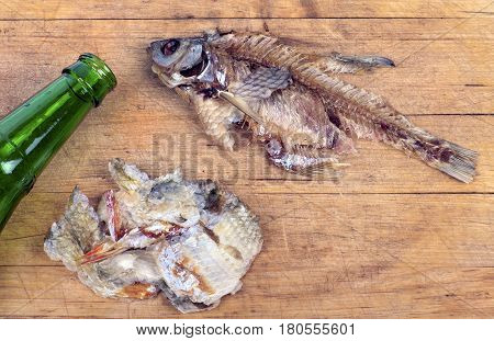 the remains of dried fish and empty beer bottle on a cutting board, closeup