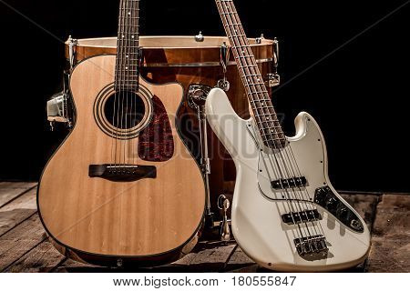 musical instruments, bass drum barrel acoustic guitar and bass guitar on a black background, the music concept