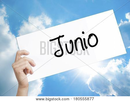 Paper With Text Junio (june In Spanish)   . Man Hand Holding Sign On White Paper. Isolated On Sky Ba