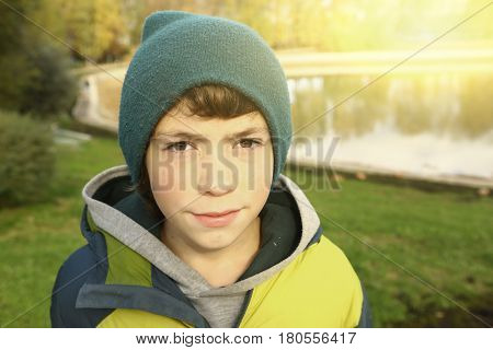 Teenager Boy In Autumn Park In Knitted Green Hat