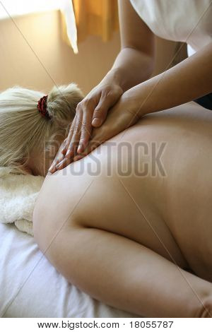 A masseur treating her client with holistic massage