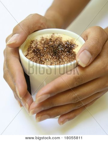 Feminine hands gently holding a mug of hot cappucino coffee with chocolate sprinkle on top