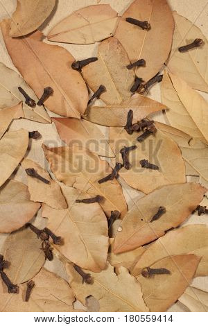 Dried bay leaves and cloves on a brown tabletop