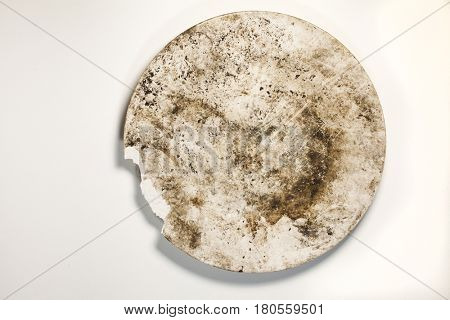 Very dirty old broken plate on a white background