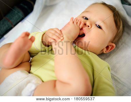 Baby hugged his leg and sucking toe