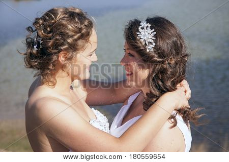 just married happy lesbian couple in white dress look each other happily in the eyes near small lake and forest on sunny day