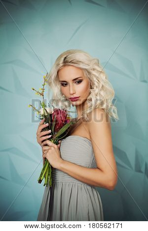 Blonde Beauty. Beautiful Woman Fashion Model with Blonde Hair Makeup and Flowers on Blue Background