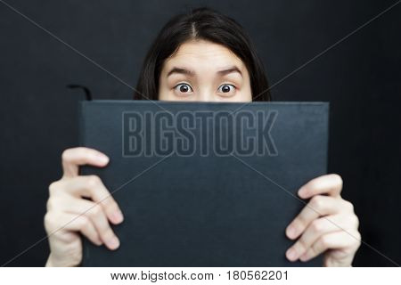 An asian girl hiding behind a black book in her hands. She is surprised. Love of reading.