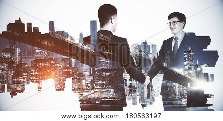 Businessmen shaking hands on abstract city background. Partnership concept. Double exposure