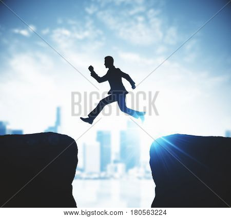 Side view of businessman silhouette jumping from cliff to cliff on blurry city and sky with sunlight background. Difficulty overcoming concept