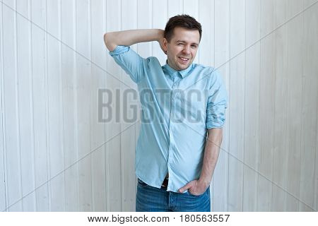 A young man in a blue shirt pensively scratches his head. Doubt about the solution