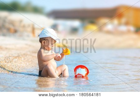 Child On The Beach Into The Sea With A Cup