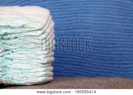 Stack of diapers or nappies on blue knitted background closeup