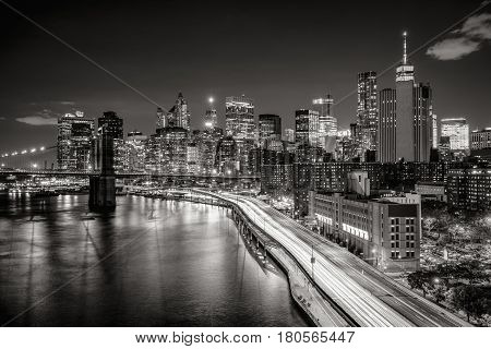 Elevated view of Lower Manhattan skyscrapers and Financial District. The Black & White night view includes the West tower of the Brooklyn Bridge East River and traffic light trails on the FDR Drive. New York City