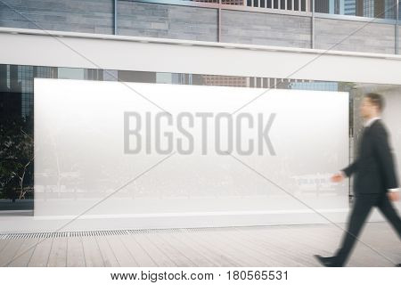 Side view of young businessman walking by glass shopfront with blank billboard during daytime. Ad concept. Mock up 3D Rendering