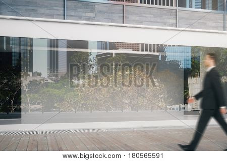 Side view of young businessman walking by shop window during daytime. Ad concept. Mock up 3D Rendering