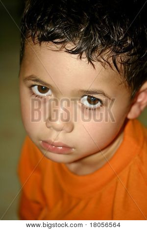 A young boy with brown eyes appears sad and unhappy