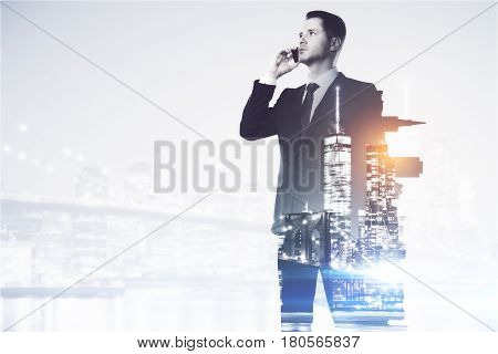 Side view of handsome young man talking on the phone on city background with copy space. Communication concept. Double exposure