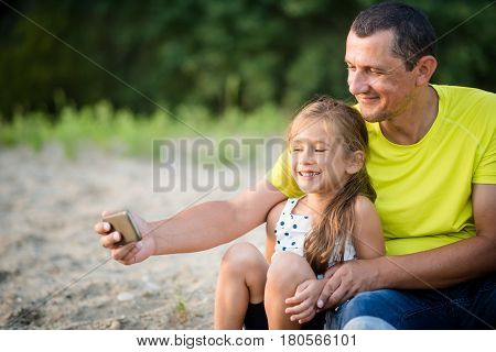 Father and his adorable little daughter taking selfie outdoors.