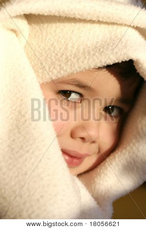 Young toddler boy plays imaginary games with his blanket,  lit by the evening glow of the sun.