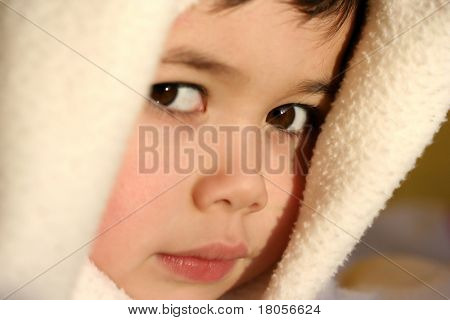 A young toddler boy plays imaginary games with his blanket, beautifully lit by the evening glow of the sun.