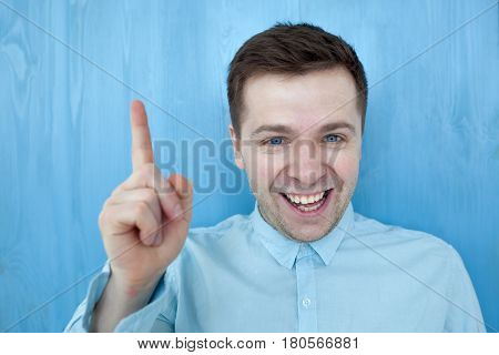 Satisfied Young Man Showing Index Finger Up, Giving Advice Or Recommendation