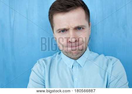 Portrait Of A Handsome Young Man In A Blue Shirt. He Squeezes His Lips Uncontrollably And Cheeks, Re