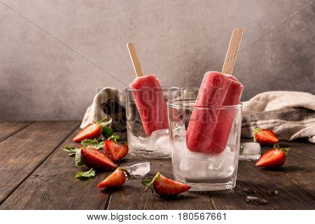 Retro style toned photo of strawberry popsicles in glass with ice on old wooden background. Healthy summer food concept with copy space.