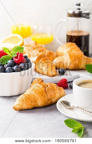 Delicious continental breakfast with fresh flaky croissants, assorted preserves, ripe berries, orange juice and coffee, close up on the croissant.