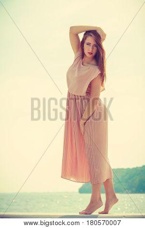 Woman Wearing Long Light Pink Dress On Jetty
