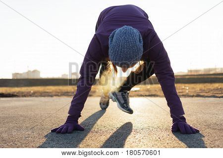 The Girl Warms Up Before Jogging, Doing A Sports Exercise In Motion. She Has Steam From Her Mouth. A