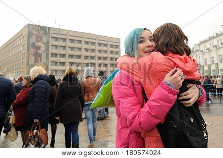 Orel Russia - April 08 2017: Meeting against terrorism. Young girls in bright clothes hugging near crowd of people closeup