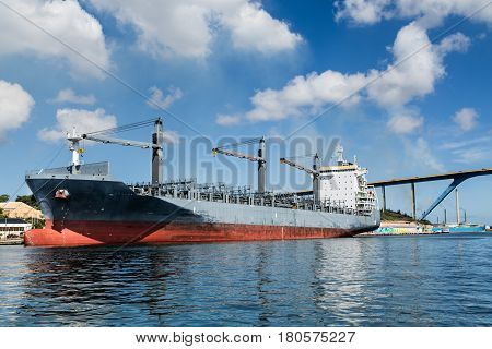 Huge Tanker Docked in Curacao Under Nice sky by bridge