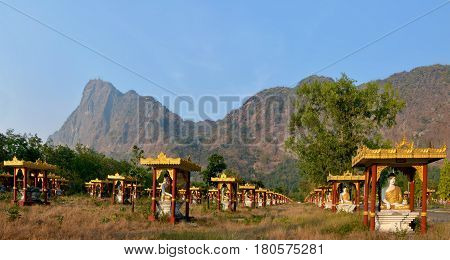 1000 Buddhas Garden At Sunset In Hpa-an, Myanmar. Mount Zwegabbin On The Background. Panoramic View.