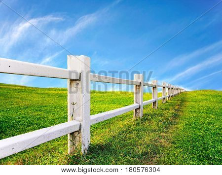 white cement fence with green grass field and blue sky in afternoon farm