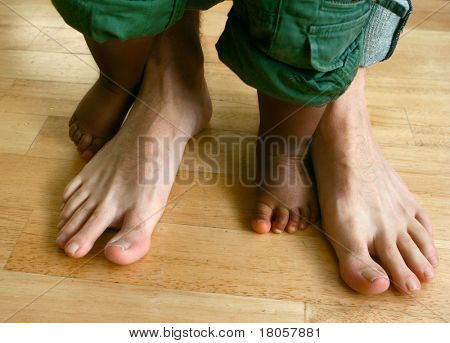 Two pair of feet belonging to a father and his son, concept of appreciation and diversity.