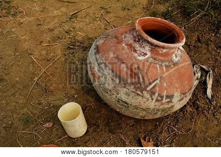 A simple handmade earthen pot used for water and a small jug sits in a field during a hot day.