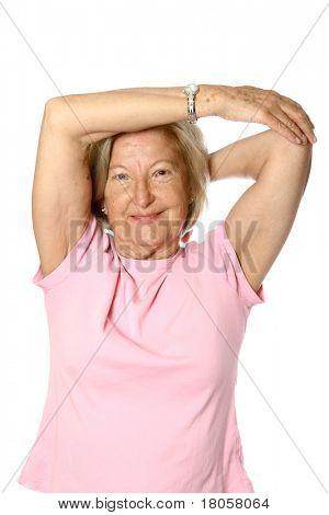 Mature caucasian female doing her exercise, stretching her triceps of left arm by pulling with another as part of healthy lifestyle, isolated on white.