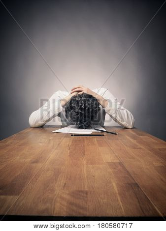 Crazy business man tired of working on a wooden office table wide angle shot with space for text or image