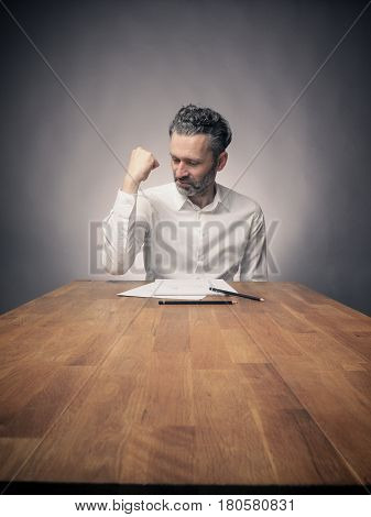 Crazy business man working on a wooden office table wide angle shot with space for text or image
