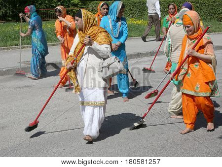 Vicenza, Vi, Italy - April 8, 2017: Barefoot Women Sikh Religious Sweeping The Street With Brooms Du