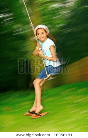 Young girl swinging fast on the rope swing tied to a tree.
