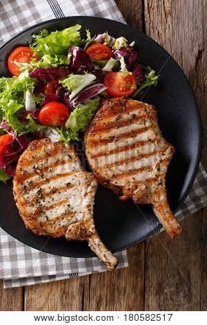 Barbecue Spicy Pork Chop With Fresh Vegetable Salad Close-up. Vertical Top View