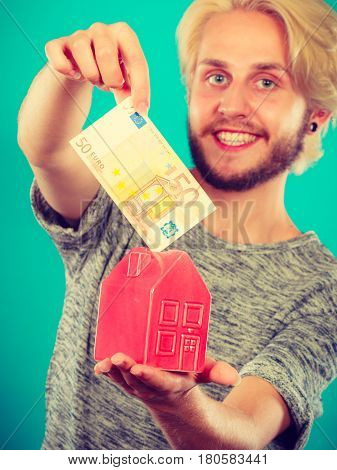 Household savings and finances economy concept. Smiling man puts money into a piggy bank in the shape of a house studio shot on blue background