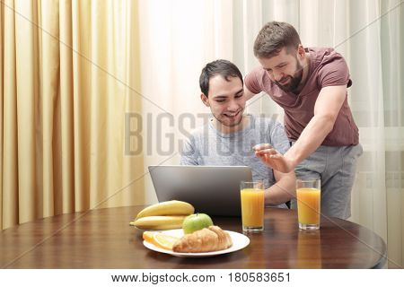 Happy gay couple having breakfast in kitchen and using laptop
